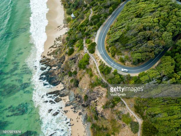 rocky outcrop into ocean with road - new south wales stock pictures, royalty-free photos & images