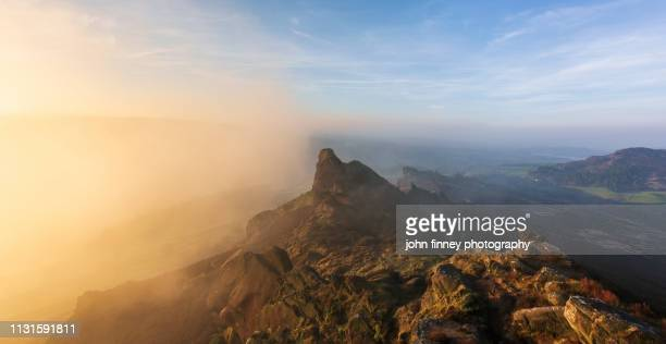 rocky pinnacle on a rugged landscape at sunrise, peak district national park. uk. - pinnacle peak stock pictures, royalty-free photos & images