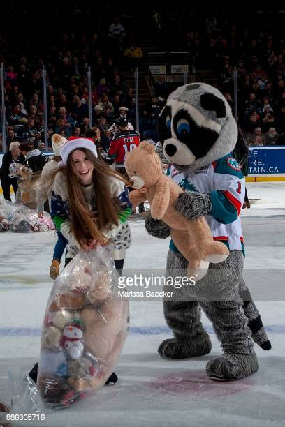 Rocky Raccoon the mascot of the Kelowna Rockets has a teddy bear fight on the ice with a volunteer cleaning up from the annual teddy bear toss...