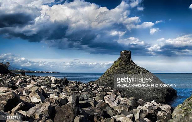 rocky seascape with dramatic clouds - acireale stock-fotos und bilder