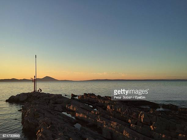 rocky shore against sky during sunset - boban stock pictures, royalty-free photos & images