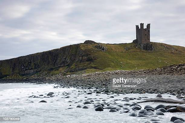 Rocky shore and ruins of Dunstanburgh Castle at Craster near Alnwick.