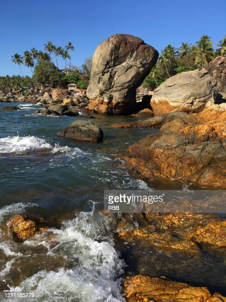 rocky shore line of palolem beach - lagoon stock pictures, royalty-free photos & images