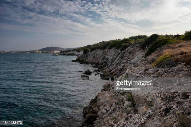 rocky shoreline with hotel buildings at the background in çeşme. - emreturanphoto stock pictures, royalty-free photos & images