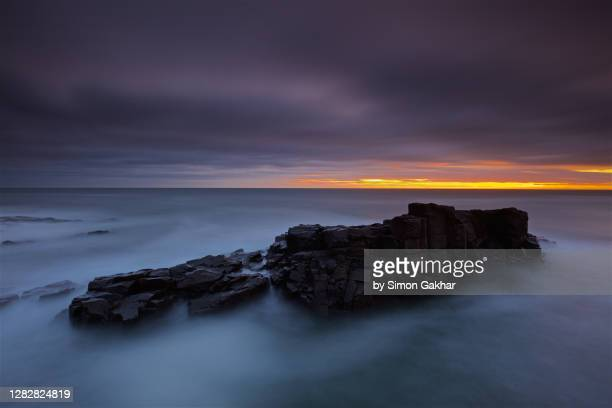 rocky sunrise seascape photograph with water motion - northumberland stock pictures, royalty-free photos & images