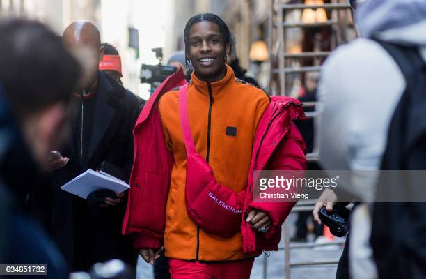 Rocky wearing a red down feather jacket, Balenciaga bag, orange zip jacket outside Calvin Klein on February 10, 2017 in New York City.