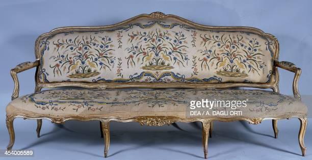 Rococo style carved and gilded sofa noncoeval fabric Rocca Meli Lupi Soragna Emilia Romagna Italy First half 18th century