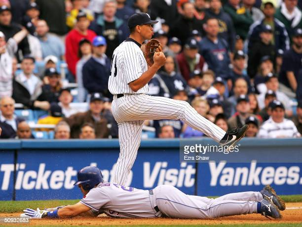 Rod Barajas of the Texas Rangers slides safely into third base below Alex Rodriguez of the New York Yankees for a triple in the ninth inning on June...