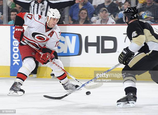 Rod Brind'Amour of the Carolina Hurricanes moves the puck up ice in front of Jordan Leopold of the Pittsburgh Penguins on March 20, 2010 at Mellon...