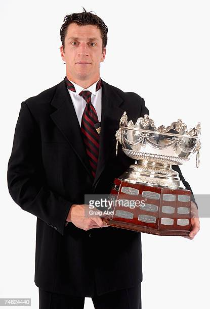 Rod Brind'Amour of the Carolina Hurricanes poses for a portrait backstage with the Frank J Selke Trophy for Top Defensive Forward in the NHL during...