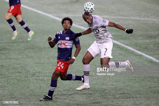 Rod Fanni of Montreal Impact wins the ball out of the air over DeJuan Jones of New England Revolution during second half of the Play-In Round match...