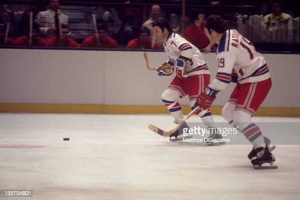 Rod Gilbert and Jean Ratelle of the New York Rangers skate the puck up the ice during an NHL game against the Montreal Canadiens circa 1972 at the...