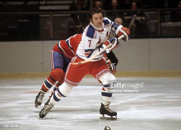 Rod Gilbert of the New York Rangers goes for the puck during an NHL game against the Montreal Canadiens circa 1974 at the Madison Square Garden in...