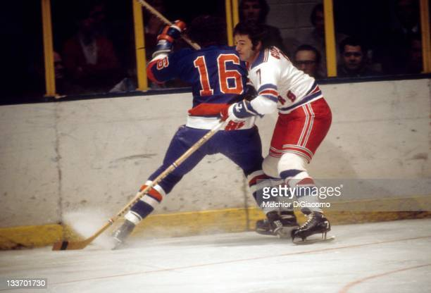 Rod Gilbert of the New York Rangers looks to check Ralph Stewart of the New York Islanders during their game circa 1973 at the Madison Square Garden...
