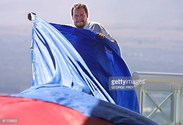Rod Hall helps unfold a 180' x 127' American flag on top of the Salt Lake Olympic Committee's 24 storey building in downtown Salt Lake City Utah 19...