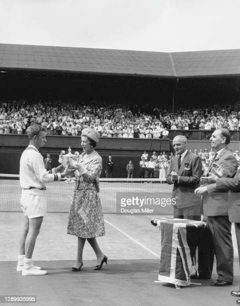 Rod Laver of Australia is presented with the Gentlemen's Singles Trophy by Princess Marina the Duchess of Kent after defeating Chuck McKinley of the...