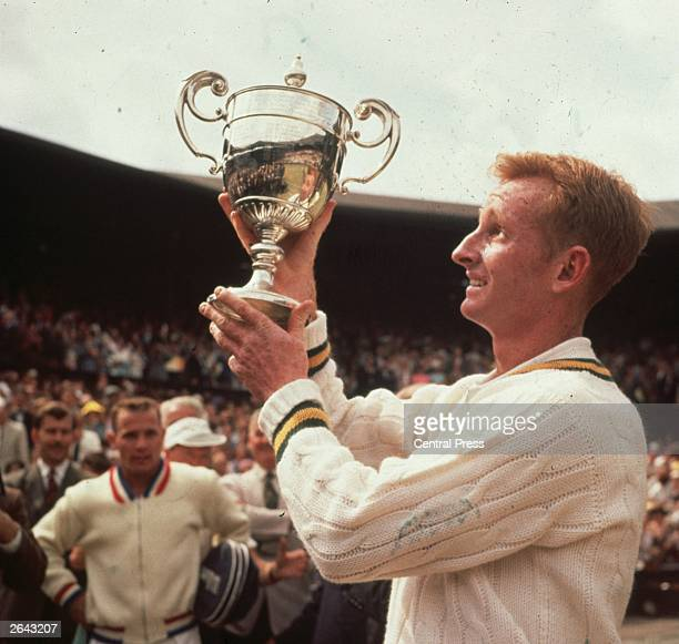 Rod Laver of Australia lifts the men's singles trophy at Wimbledon after beating Chuck McKinley of the USA