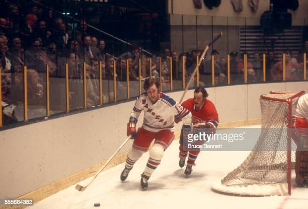Rod Seiling of the New York Rangers skates around the net with the puck as Yvan Cournoyer of the Montreal Canadiens follows behind during an NHL game...