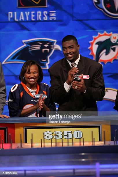 Rod Smith of the Denver Broncos smiles and applauds with his favorite Broncos fan during the Wheel of Fortune NFL Players Week taping on December 7...