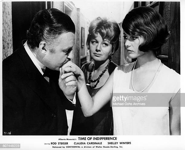 Rod Steiger kisses Claudia Cardinale hand as Shelley Winters stands in between in a scene from the movie 'Time of Indifference' circa 1964