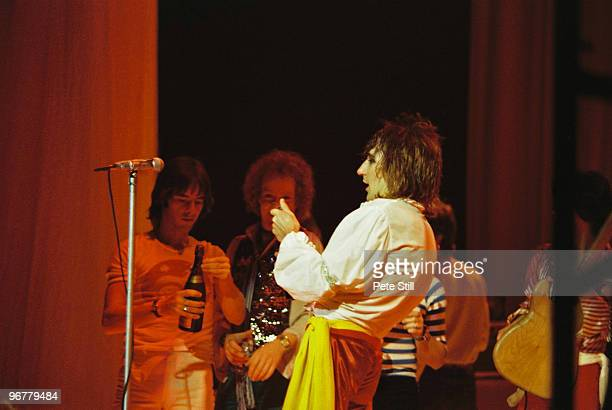 Rod Stewart opens a bottle of champagne on his birthday during his performance on stage at The Playhouse Theatre while band members Ian McLagan and...
