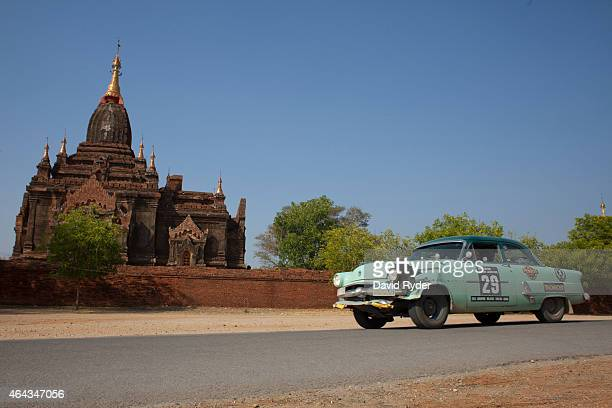 Rod Wade and Jackson Evans pass by a pagoda in a 1953 Ford Crestline during the final day of the Road to Mandalay 24day car rally through southeast...