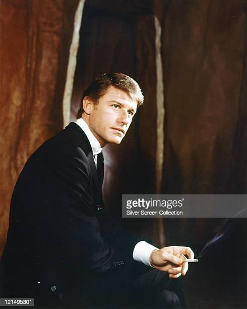 Roddy McDowall British actor wearing a black suit with a white shirt and black tie and holding a lit cigarette in a studio portrait circa 1965