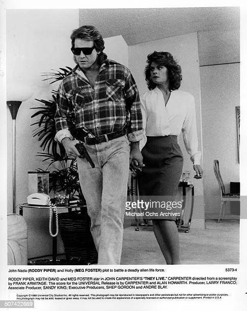 Roddy Piper and Meg Foster run from deadly alien live forces in a scene from the Universal Studio movie They Live circa 1988