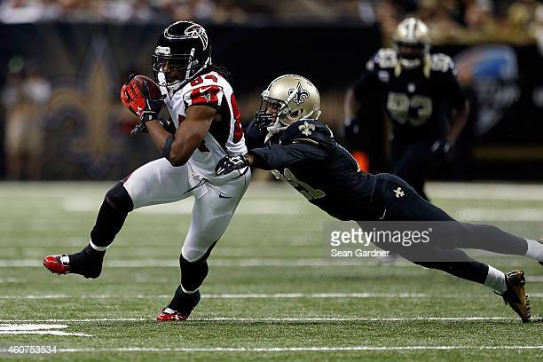 Roddy White of the Atlanta Falcons is brought down by Patrick Robinson of the New Orleans Saints during the third quarter of a game at the...