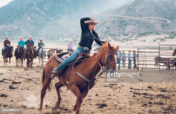 Acción de rodeo vaquera persiguiendo el toro con lazo en Arena