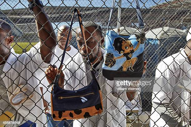 Angola Prison Rodeo View of inmate Anthony Mandingo selling handmade purses to attendees through a chain link fence in the Arts Crafts Market at...