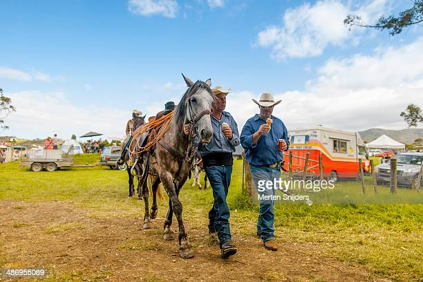 Rodeo cowboys keep it cool with an icecream whhile guiding their horse down a sandy path at Far North Rodeo, Kaitaia, Northland