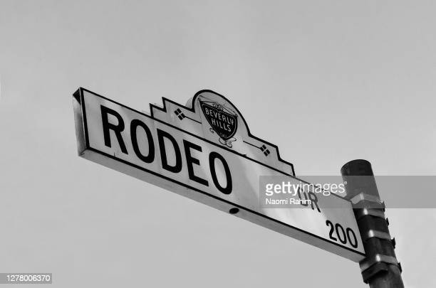 rodeo drive street sign on a clear day in black & white - beverly hills, los angeles, california - los angeles stock pictures, royalty-free photos & images