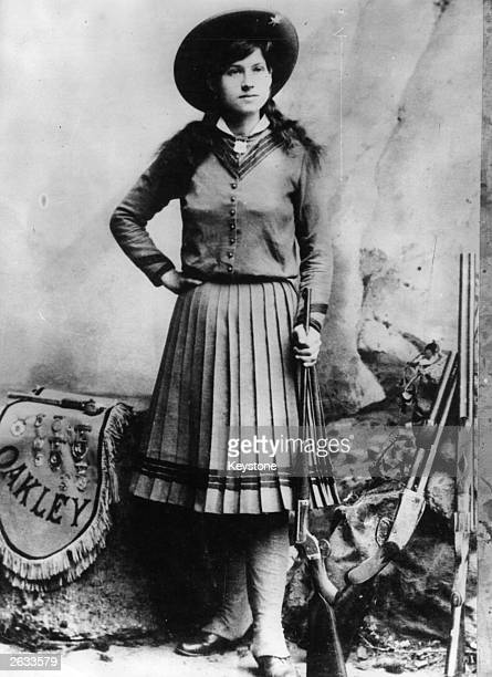 US rodeo star Annie Oakley who was famous as a highly skilled trick shooter with the Buffalo Bill Wild West Show One of her tricks was to shoot...