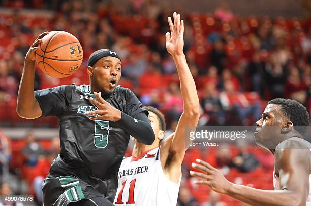 Roderick Bobbitt of the Hawaii Warriors looks to pass while guarded by Zach Smith of the Texas Tech Red Raiders during the game on November 28 2015...