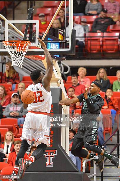 Roderick Bobbitt of the Hawaii Warriors passes the ball around Norense Odiase of the Texas Tech Red Raiders during the game on November 28 2015 at...