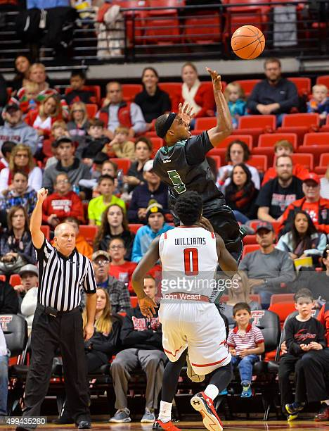 Roderick Bobbitt of the Hawaii Warriors shoots the ball while guarded by Devaugntah Williams of the Texas Tech Red Raiders during the game on...