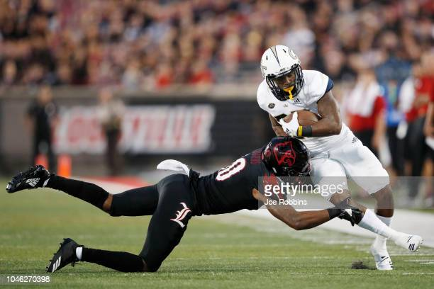 Rodjay Burns of the Louisville Cardinals makes a tackle near the sideline against Clinton Lynch of the Georgia Tech Yellow Jackets in the first half...