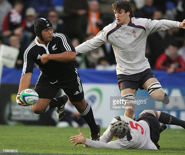 Rodney Ah You offloads the ball as he is tackled by Josh Turnbull and Sam Warburton during the IRB under 19 World Championship semi final match...
