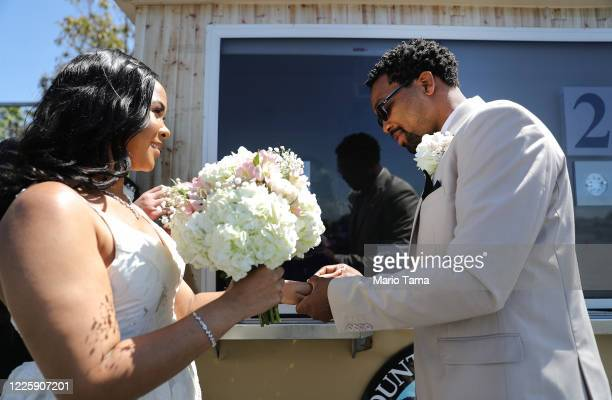Rodney and Monica Cosby exchange rings as they take marriage vows at a pop-up socially distanced marriage booth, in the parking lot of the Honda...