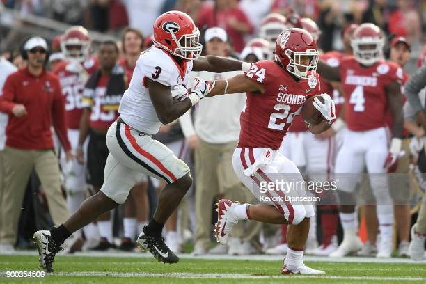 Rodney Anderson of the Oklahoma Sooners breaks away from Roquan Smith of the Georgia Bulldogs in the 2018 College Football Playoff Semifinal Game...