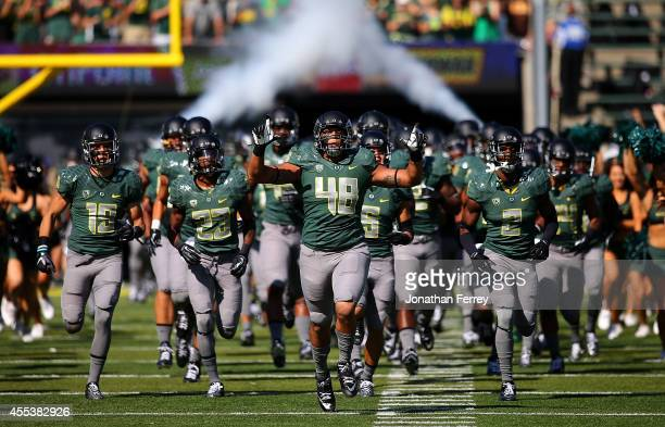 Rodney Hardick of the Oregon Ducks leads the team onto the field against the Wyoming Cowboys at Autzen Stadium on September 13 2014 in Eugene Oregon