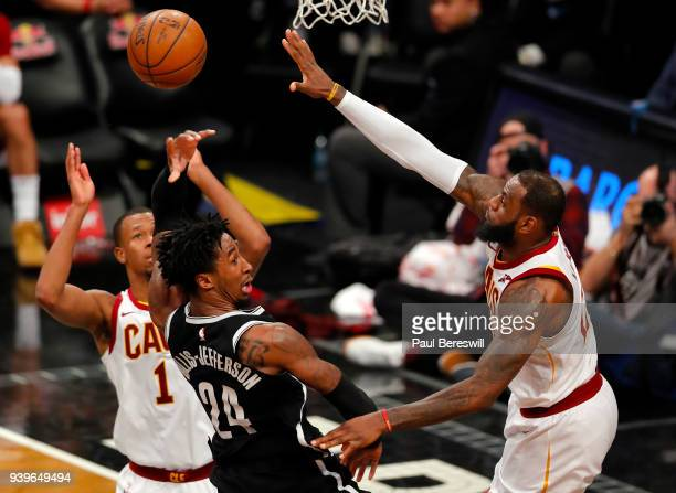 Rodney Hood and LeBron James of the Cleveland Cavaliers pressure Milton Doyle of the Brooklyn Nets in an NBA basketball game on March 25 2018 at...