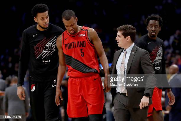 Rodney Hood of the Portland Trail Blazers is helped off the floor after being injured against the Denver Nuggets in the third quarter during Game...