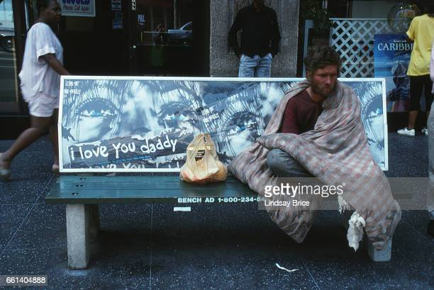 Rodney King Riot. A view of a dazed young man wrapped in quilt sitting on bench amidst passersby on Hollywood Boulevard after two nights of fires and...