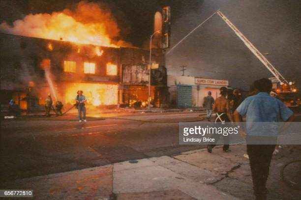 Rodney King Riot A view of firemen attempting to put out fire of burning businesses with fire truck and crane on Pico Boulevard during the Rodney...
