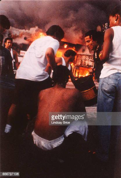 Rodney King Riot. Citizens joining together, forming a bucket brigade, frantically attempting to put out raging fire at intersection of Pico...