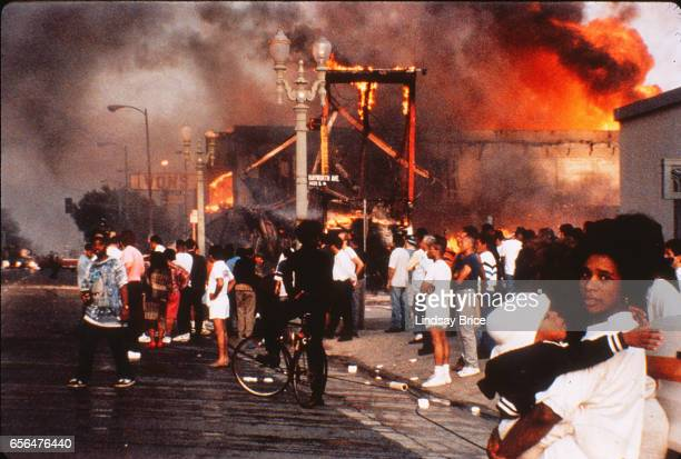 Rodney King Riot Mother and child amidst mayhem businesses burning bystanders watching raging fires pedestrian walking in the street drinking from a...
