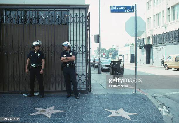 Rodney King Riot. Two LAPD officers in riot helmets standing guard on Hollywood Boulevard's Walk of Fame the morning after fires and looting reached...