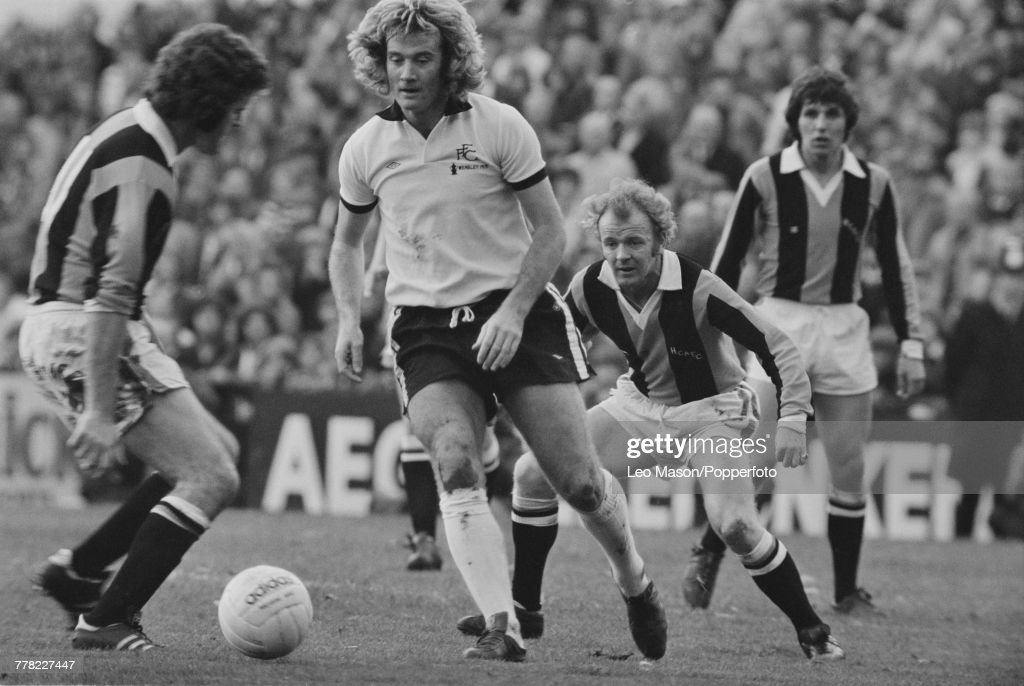 Rodney Marsh of Fulham FC pictured in centre making a run with the ball as Billy Bremner (1942-1997) of Hull City AFC, 3rd from left, looks on during the League Division Two game between Fulham and Hull City at Fulham's Craven Cottage ground in London on 10th April 1976. The match would end in a 1-1 draw.